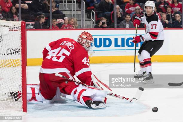 Goaltender Jonathan Bernier of the Detroit Red Wings makes a save as Kenny Agostino of the New Jersey Devils looks for the rebound during an NHL game...