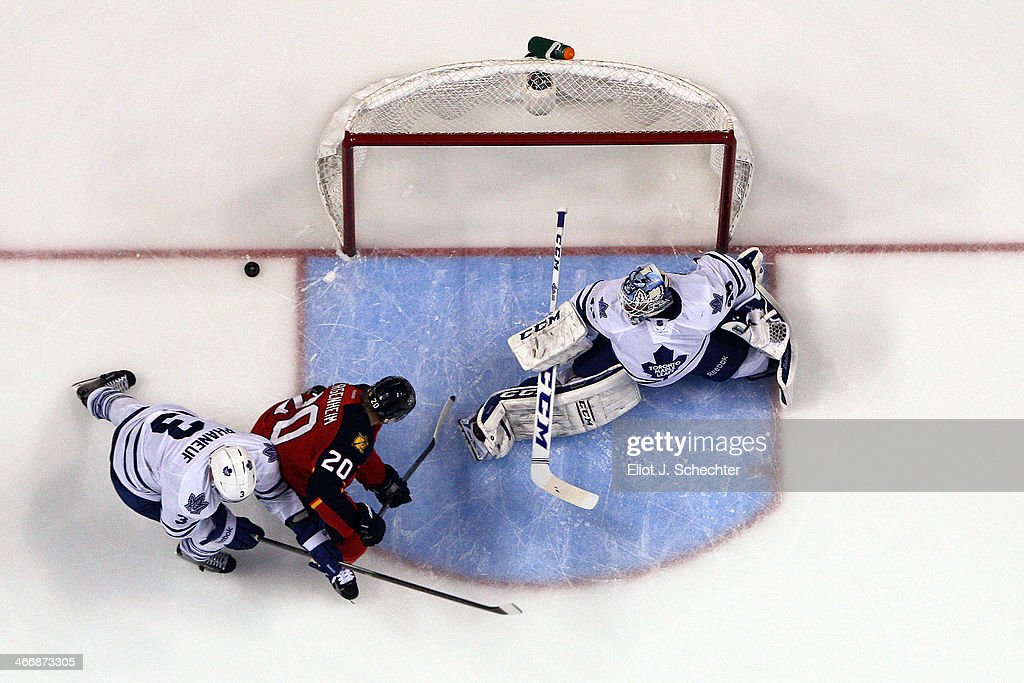Goaltender Jonathan Bernier #45 of the Toronto Maple Leafs defends the net with help from teammate Dion Phaneuf #3 against Sean Bergenheim #20 of the Florida Panthers at the BB&T Center on February 4, 2014 in Sunrise, Florida.