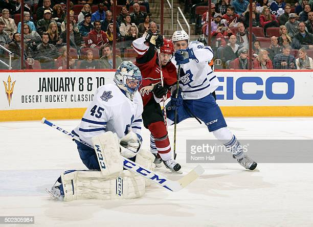 Goaltender Jonathan Bernier of the Toronto Maple Leafs makes a glove save as Tobias Rieder of the Arizona Coyotes and Frank Corrado of the Maple...