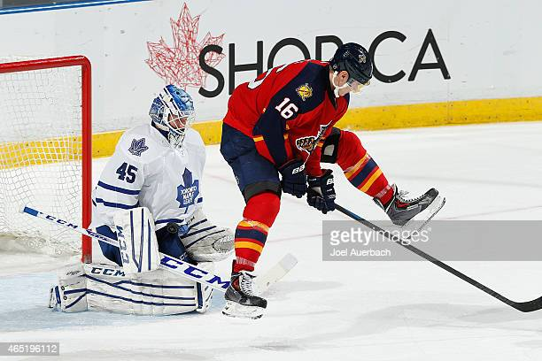 Goaltender Jonathan Bernier of the Toronto Maple Leafs stops a shot that goes past Aleksander Barkov of the Florida Panthers during third period...
