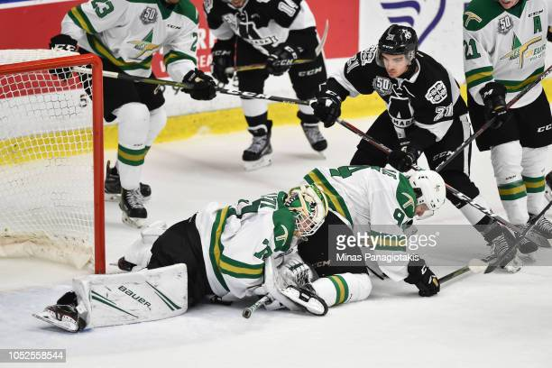 Goaltender Jonathan Lemieux of the ValdOr Foreurs smothers the puck while teammate Alexandre Couture helps defend the net against Antoine Rochon of...