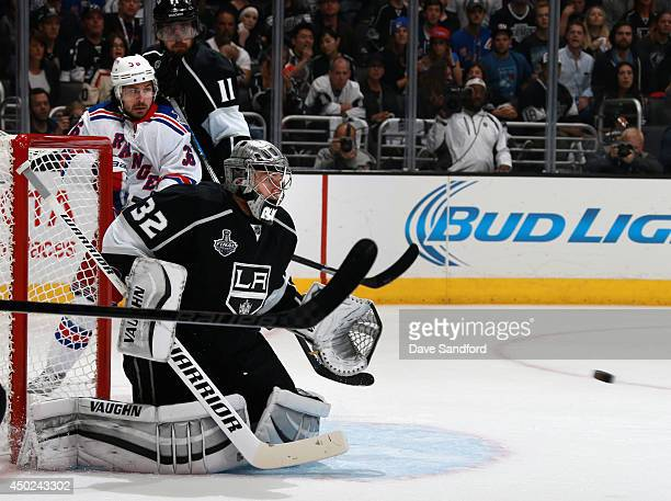 Goaltender Jonathan Quick and Anze Kopitar of the Los Angeles Kings watch a shot as Mats Zuccarello of the New York Rangers waits for the rebound to...