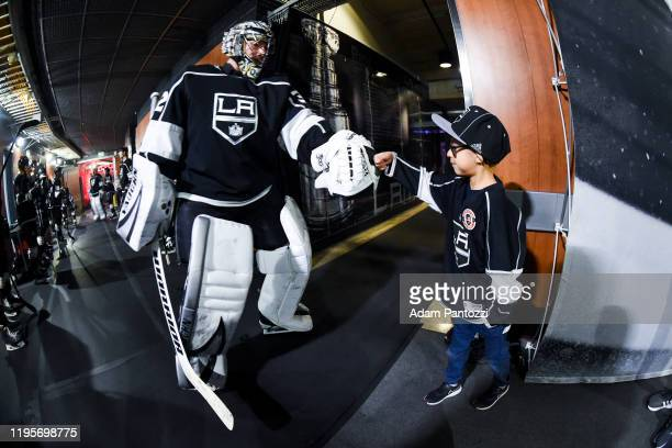 Goaltender Jonathan Quick of the Los Angeles Kings and a young Kings fan fist bump as Quick takes the ice for warm-up before the game against the St....