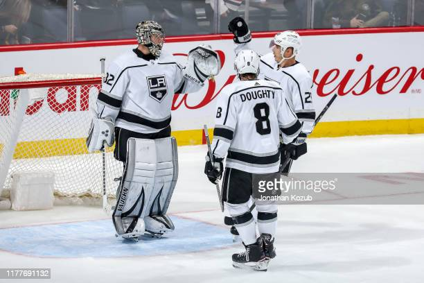 Goaltender Jonathan Quick of the Los Angeles Kings celebrates a 3-2 victory over the Winnipeg Jets with teammates Drew Doughty and Dustin Brown at...