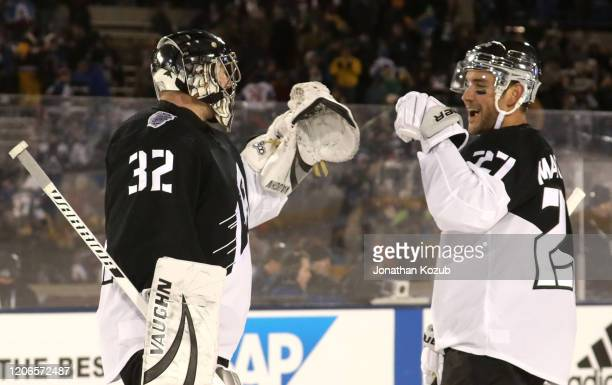 Goaltender Jonathan Quick of the Los Angeles Kings celebrates with Alec Martinez on the ice after the 2020 NHL Stadium Series game between the Los...