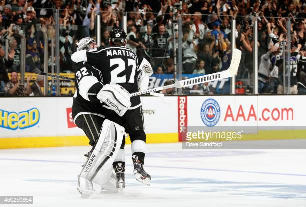 Goaltender Jonathan Quick of the Los Angeles Kings celebrates with Alec Martinez after Dustin Brown scored the overtime goal to defeat the New York...