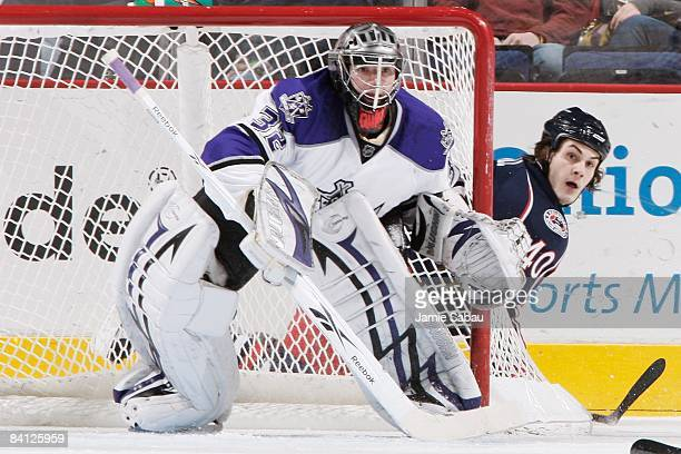 Goaltender Jonathan Quick of the Los Angeles Kings guards the net as forward Jared Boll of the Columbus Blue Jackets looks out from behind the net on...