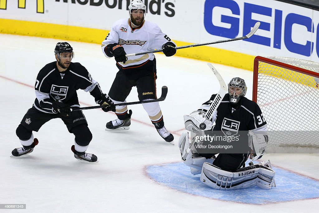 Goaltender Jonathan Quick #32 of the Los Angeles Kings makes a save as defenseman Alec Martinez #27 of the Los Angeles Kings and Patrick Maroon #62 of the Anaheim Ducks look on during the third period of Game Six of the Second Round of the 2014 NHL Stanley Cup Playoffs at Staples Center on May 14, 2014 in Los Angeles, California.
