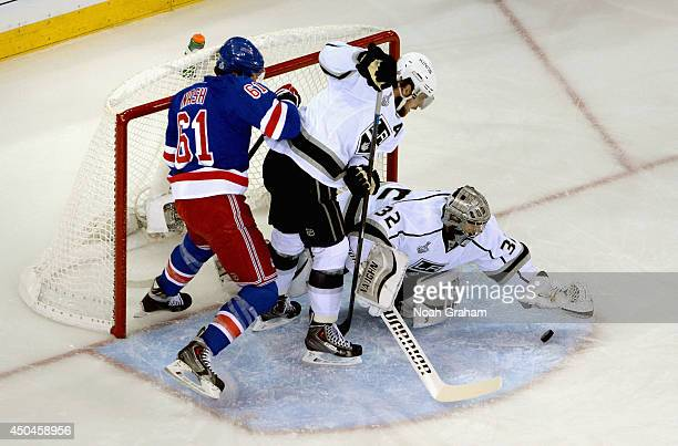 Goaltender Jonathan Quick of the Los Angeles Kings makes a save in front of teammate Anze Kopitar and Rick Nash of the New York Rangers in the first...
