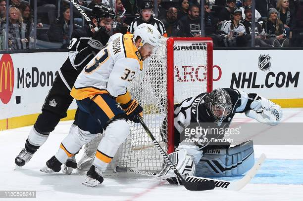 Goaltender Jonathan Quick of the Los Angeles Kings makes a save against Viktor Arvidsson of the Nashville Predators as Alec Martinez of the Los...