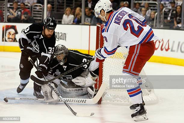 Goaltender Jonathan Quick of the Los Angeles Kings makes a stick save between Justin Williams and Chris Kreider of the New York Rangers during the...