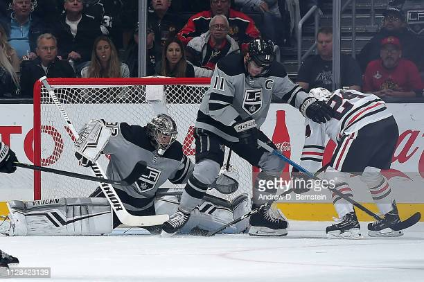 Goaltender Jonathan Quick of the Los Angeles Kings makes the save against Dominik Kahun of the Chicago Blackhawks with help from Anze Kopitar of the...