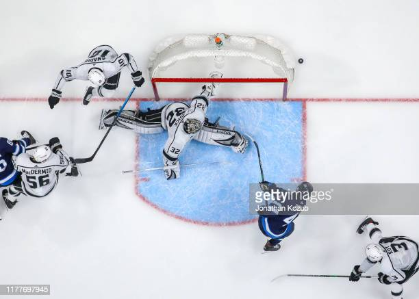 Goaltender Jonathan Quick of the Los Angeles Kings slides across the crease as a shot by Neal Pionk of the Winnipeg Jets goes wide of the net during...