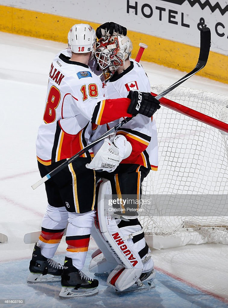 Goaltender Joni Ortio #37 of the Calgary Flames is congratulated by Matt Stajan #18 of the Calgary Flames after defeating the Arizona Coyotes 4-1 in the NHL game at Gila River Arena on January 15, 2015 in Glendale, Arizona.