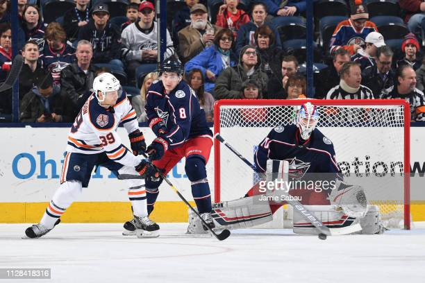 Goaltender Joonas Korpisalo of the Columbus Blue Jackets defends the net as Alex Chiasson of the Edmonton Oilers passes the puck away from Zach...