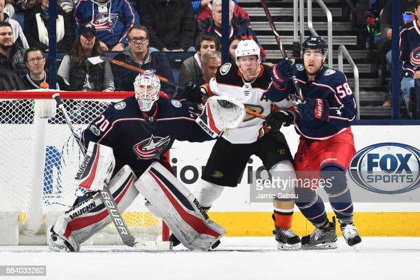 Goaltender Joonas Korpisalo of the Columbus Blue Jackets defends the net as Corey Perry of the Anaheim Ducks and David Savard of the Columbus Blue...
