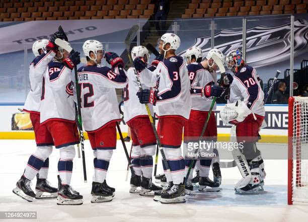 Goaltender Joonas Korpisalo of the Columbus Blue Jackets is congratulated by teammates after defeating the Toronto Maple Leafs 3-0 to clinch the...