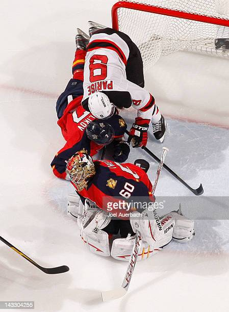 Goaltender Jose Theodore stops a shot as Dmitry Kulikov of the Florida Panthers defends against Zach Parise of the New Jersey Devils in Game Five of...
