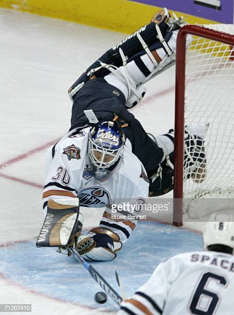 Goaltender Jussi Markkanen of the Edmonton Oilers makes a diving stop on the puck during game five of the 2006 NHL Stanley Cup Finals against the...