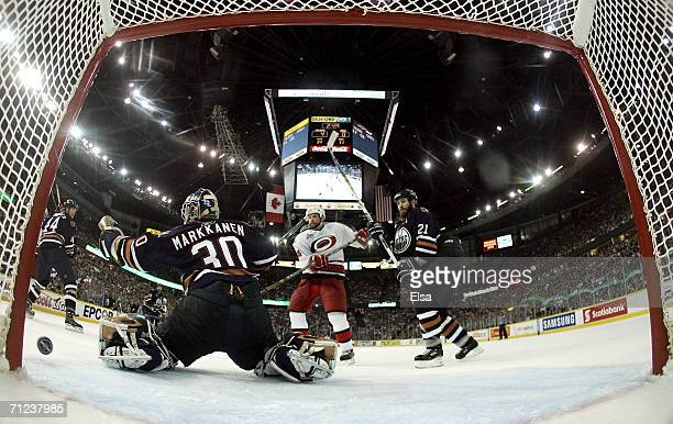 Goaltender Jussi Markkanen of the Edmonton Oilers protects the goal against Aaron Ward of the Carolina Hurricanes during game six of the 2006 NHL...