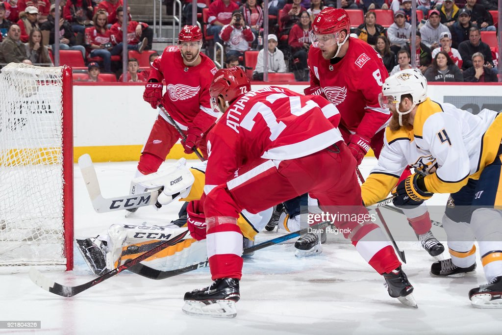 Goaltender Juuse Saros #74 of the Nashville Predators makes an initial pad save on a battle for the puck as teammate Ryan Ellis #4 defends against Andreas Athanasiou #72, Justin Abdelkader #8 and Tomas Tatar #21 of the Detroit Red Wings during an NHL game at Little Caesars Arena on February 20, 2018 in Detroit, Michigan.