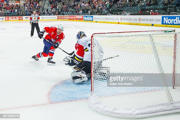Goaltender Kaaop Kahkonen of Espoo Blues in action with Ronny Arendt of Adler Mannheim during the Champions Hockey League round of thirty-two game...
