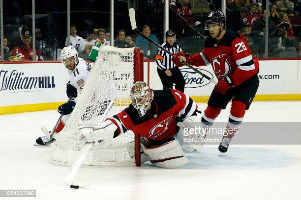 Goaltender Keith Kinkaid of the New Jersey Devils defends the net with the help of teammate Damon Severson against Jonathan Huberdeau of the Florida...