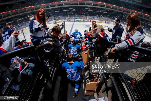 Goaltender Laurent Brossoit Mathieu Perreault and Tyler Myers of the Winnipeg Jets hit the ice for the start of the pregame warm up prior to NHL...