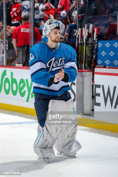 Goaltender Laurent Brossoit of the Winnipeg Jets applauds the fans as he leaves the ice after receiving second star honours following a 42 victory...