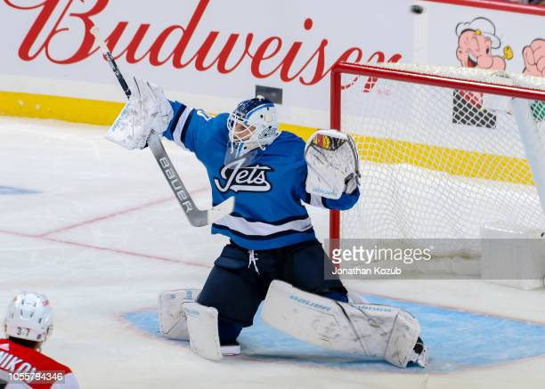 Goaltender Laurent Brossoit of the Winnipeg Jets deflects the puck over the net during third period action against the Carolina Hurricanes at the...