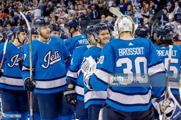 Goaltender Laurent Brossoit of the Winnipeg Jets gets congratulated by teammates following a 63 victory over the Chicago Blackhawks at the Bell MTS...