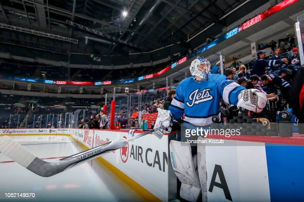 Goaltender Laurent Brossoit of the Winnipeg Jets hits the ice for the start of the pregame warm up prior to NHL action against the Carolina...