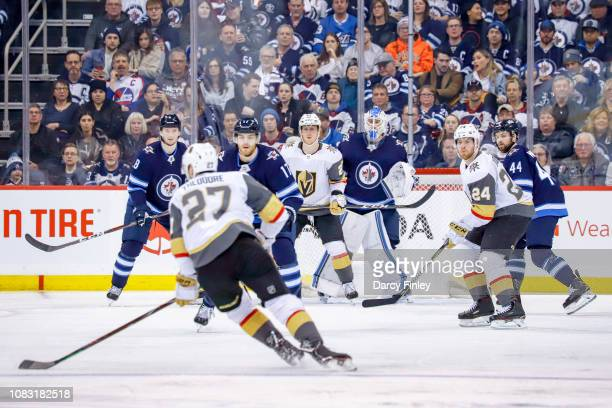 Goaltender Laurent Brossoit of the Winnipeg Jets looks around a screen as Shea Theodore of the Vegas Golden Knights plays the puck at the point...