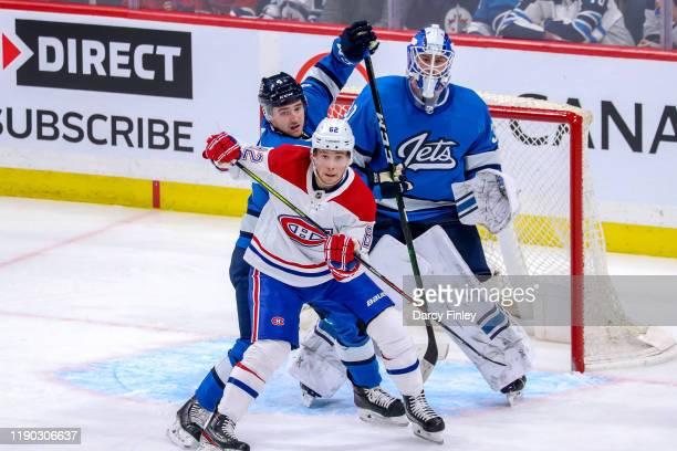 Goaltender Laurent Brossoit of the Winnipeg Jets looks around a screen set by teammate Neal Pionk as he battles Artturi Lehkonen of the Montreal...
