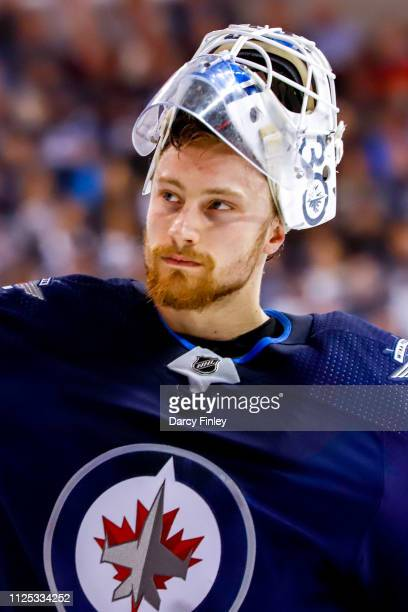 Goaltender Laurent Brossoit of the Winnipeg Jets looks on during a third period stoppage in play against the Ottawa Senators at the Bell MTS Place on...