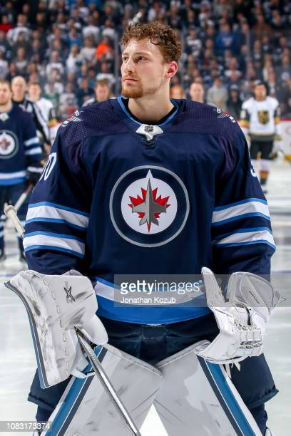 Goaltender Laurent Brossoit of the Winnipeg Jets looks on during the singing of the National anthems prior to puck drop against the Vegas Golden...