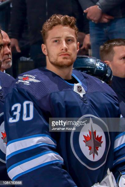 Goaltender Laurent Brossoit of the Winnipeg Jets looks on from the bench prior to puck drop against the Tampa Bay Lightning at the Bell MTS Place on...