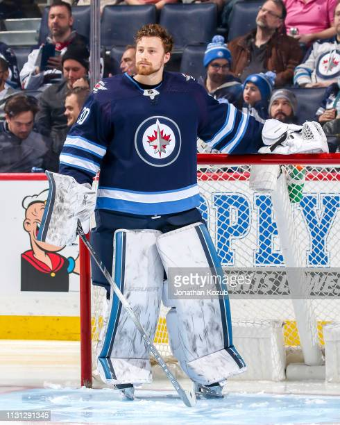 Goaltender Laurent Brossoit of the Winnipeg Jets looks on from the crease prior to puck drop against the Ottawa Senators at the Bell MTS Place on...