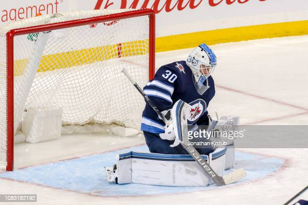 Goaltender Laurent Brossoit of the Winnipeg Jets makes a glove save during second period action against the Vegas Golden Knights at the Bell MTS...