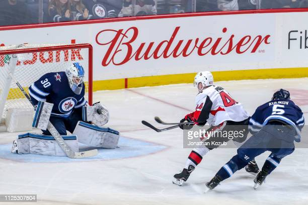 Goaltender Laurent Brossoit of the Winnipeg Jets makes a glove save on a shot by JeanGabriel Pageau of the Ottawa Senators during second period...