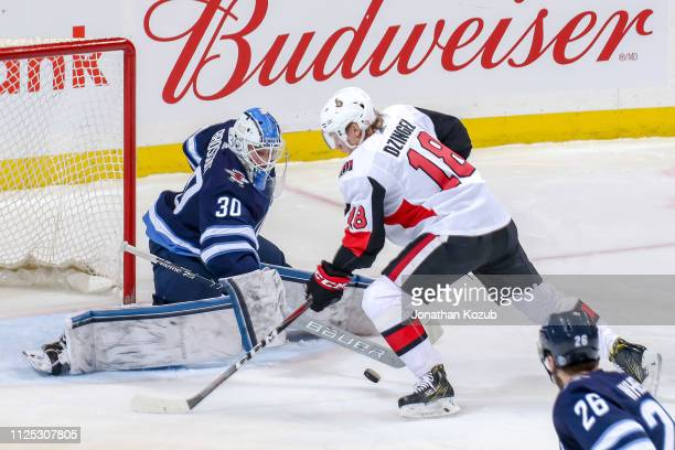 Goaltender Laurent Brossoit of the Winnipeg Jets makes a stick save on Ryan Dzingel of the Ottawa Senators during second period action at the Bell...
