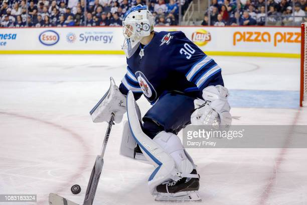 Goaltender Laurent Brossoit of the Winnipeg Jets plays the puck during third period action against the Vegas Golden Knights at the Bell MTS Place on...