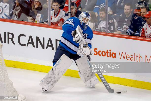 Goaltender Laurent Brossoit of the Winnipeg Jets plays the puck behind the net during second period action against the Detroit Red Wings at the Bell...