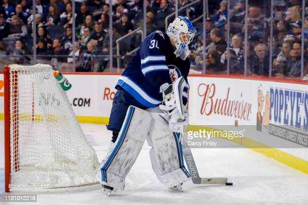 Goaltender Laurent Brossoit of the Winnipeg Jets plays the puck behind the net during third period action against the Ottawa Senators at the Bell MTS...