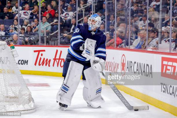 Goaltender Laurent Brossoit of the Winnipeg Jets plays the puck behind the net during third period action against the Pittsburgh Penguins at the Bell...