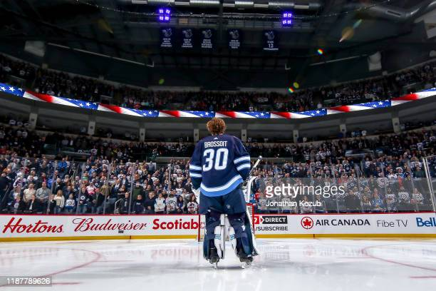 Goaltender Laurent Brossoit of the Winnipeg Jets stands on the ice during the singing of the National anthems prior to puck drop against the Detroit...
