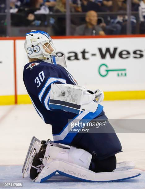 Goaltender Laurent Brossoit of the Winnipeg Jets stretches in the crease during a third period stoppage in play against the Vegas Golden Knights at...