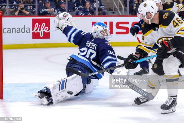 Goaltender Laurent Brossoit of the Winnipeg Jets stretches out to make a pad save on David Krejci of the Boston Bruins during third period action at...