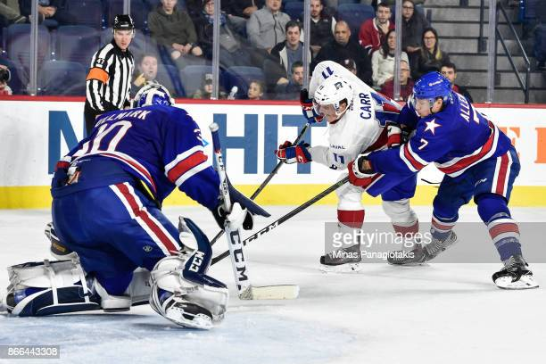 Goaltender Linus Ullmark defends his net as Daniel Carr of the Laval Rocket skates the puck against Conor Allen of the Rochester Americans during the...