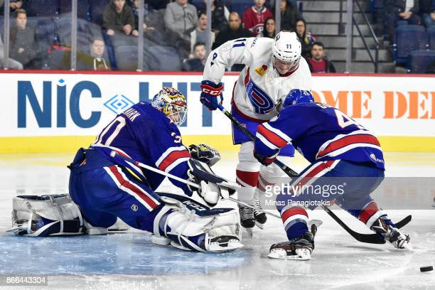 Goaltender Linus Ullmark of the Rochester Americans makes a save near Daniel Carr of the Laval Rocket during the AHL game at Place Bell on October 25...